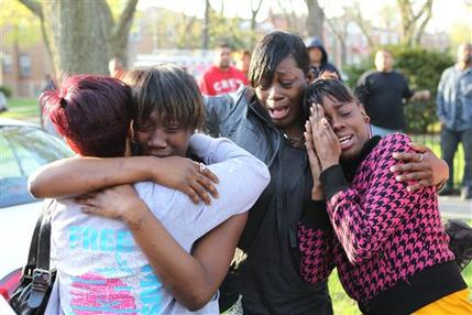 Shakeitha Myers, second from left, Pamela Jackson and Delores Ousley, right, cry early Wednesday, April 14, 2010 outside the crime scene at a Marquette neighborhood residence on the southwest side of Chicago. A gunman entered a home early Wednesday, fatally shooting four people, three of them children, and wounding two others, city police said. (AP Photo/Chicago Tribune, Alex Garcia)
