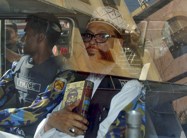 Sayedee, vice-president of the Jamaat-e-Islami party, sits inside a vehicle next to a police officer on his way to a court in Dhaka