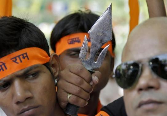 Members from Bajrang Dal and VHP hold a trident during a protest in New Delhi