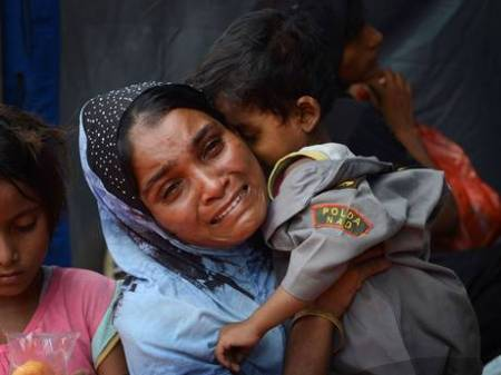 A migrant Rohingya woman from Myanmar breaks down while holding her son at Kuala Langsa in Aceh province