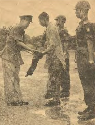 A Mujahideen leader surrendered arm to Brigadier Aung Gyi as part of the government's peace process in Buthidaung, Arakan, on 4 July 1961