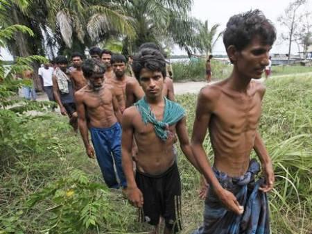 Bangladeshi migrants walk toward a temporary shelter al at Kuala Langsa Port in Langsa