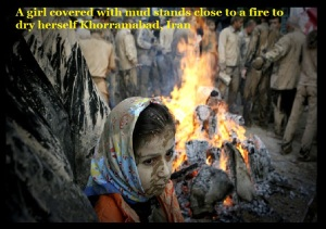 A girl covered with mud stands close to a fire to dry herself Khorramabad, Iran