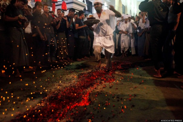 In this photo taken on Monday, Nov. 11, 2013, Myanmar Shia Muslim walks across burning embers during the Ashura festival in Yangon, Myanmar. Shia Muslims mark the Day of Ashura as a day of mourning for the death of the grandson of Prophet Muhammad. Devotees recite prayers, flagellate themselves and walk on fire to mark the day of mourning. (AP Photo/Khin Maung Win)