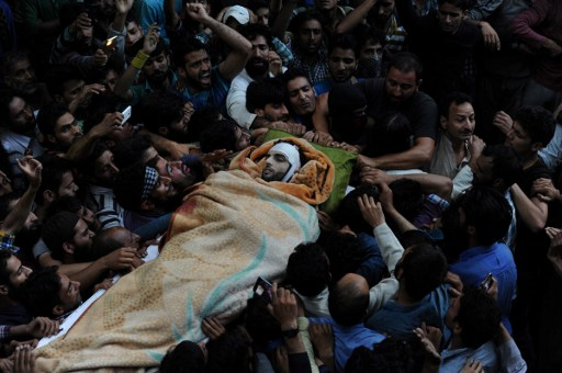 Kashmiri mourners carry the body of Burhan Muzaffar Wani, the new-age poster boy for the rebel movement in the restive Himalayan state of Jammu and Kashmir, ahead of his funeral in Tral, his native town, 42kms south of Srinagar on July 9, 2016. A top commander from the largest rebel group in Indian-administered Kashmir was killed in a gun battle with government forces on July 8, police said. Young and media savvy, Burhan Wani was a top figure in Hizbul Mujahideen and had a one million rupee ($14,900) bounty on his head. Wani, 22, joined the rebel movement at the age of 15 and in recent years had been behind a huge recruitment drive to the group's ranks, attracting young and educated Kashmiris to the decades-old fight for independence of the restive disputed region. Viewed locally as a hero, his death sparked protests in nearby Anantnag town, with hundreds taking to the streets shouting independence slogans and lauding Wani as a revolutionary, witnesses said. / AFP PHOTO / TAUSEEF MUSTAFA